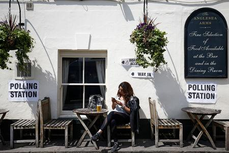 A woman enjoys a beer outside The Anglesea Arms which has been turned into a polling station for the European elections, taking place despite Brexit uncertainty, in London