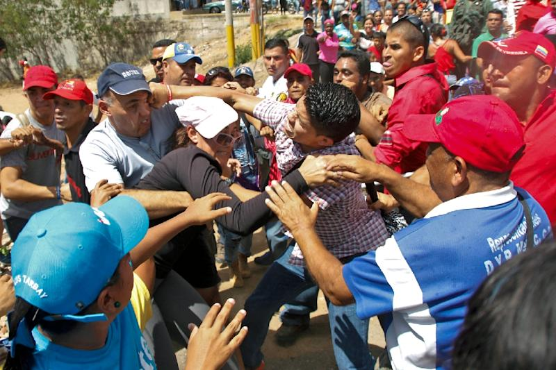 Venezuelan Government' supporters (R) clash against President Maduro opponents during a demonstration to demand a recall referendum against Maduro