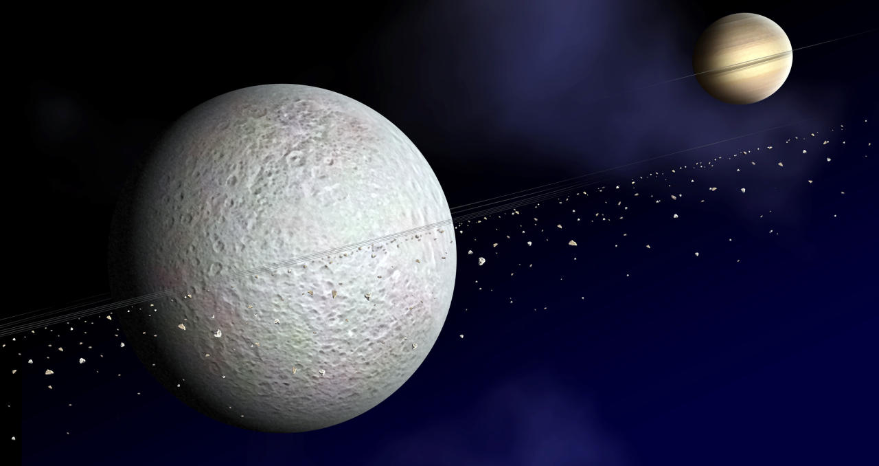 This artist's conception provided by NASA shows the ring of debris that may orbit Saturn's second-largest moon, Rhea, shown at left. These new observations, detected by the Cassini spacecraft suggest Saturn's second-largest moon may be surrounded by rings, possibly the first time a ring system has been found around a moon. (AP Photo/NASA/JPL/JHUAPL)
