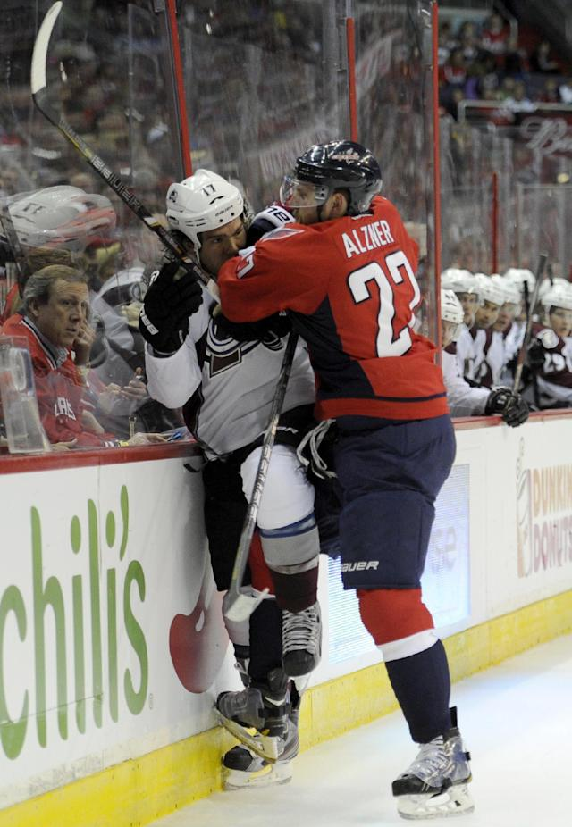 Washington Capitals defenseman Karl Alzner (27) checks Colorado Avalanche right wing Steve Downie (17) into the boards during the second period an NHL hockey game, Saturday, Oct. 12, 2013, in Washington. (AP Photo/Nick Wass)