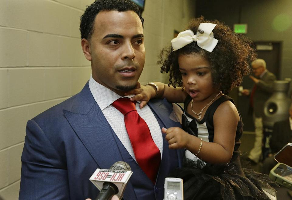 Seattle Mariners' Nelson Cruz holds his daughter, Giada, 2, as he talks to reporters after being introduced at a baseball news conference, Thursday, Dec. 4, 2014, in Seattle. (AP Photo/Ted S. Warren)