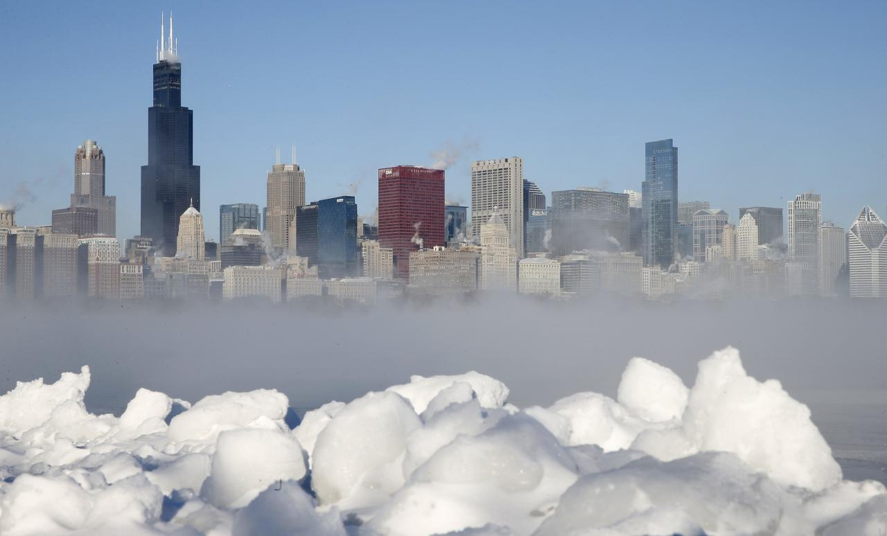 The Chicago skyline is seen beyond the arctic sea smoke rising off Lake Michigan in Chicago, Illinois, January 6, 2014. A blast of Arctic air gripped the mid-section of the United States on Monday, bringing the coldest temperatures in two decades, forcing businesses and schools to close and causing widespread airline delays and hazardous driving conditions. Meteorologists said temperatures were dangerously cold and life-threatening in some places, with 0 degrees Fahrenheit (minus 18 Celsius) recorded in Chicago, St. Louis and Indianapolis. The chill was set to bear down on eastern and southern states as the day wore on. REUTERS/Jim Young (UNITED STATES - Tags: ENVIRONMENT CITYSCAPE TPX IMAGES OF THE DAY)