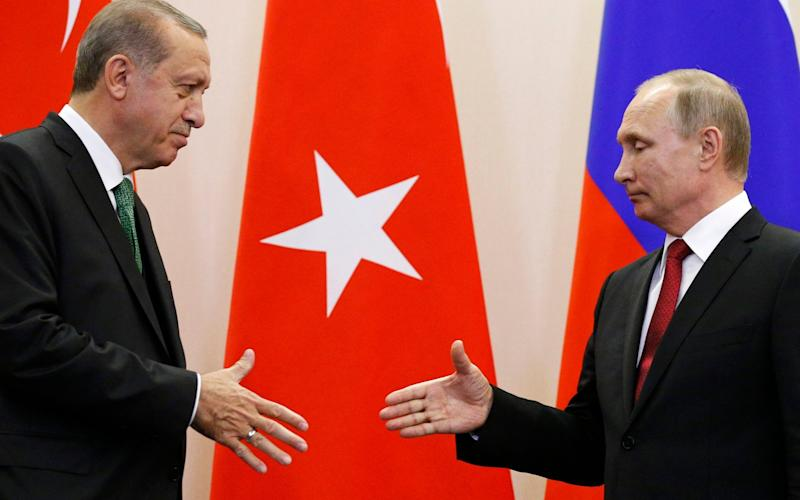 Russian President Vladimir Putin, right, and Turkish President Recep Tayyip Erdogan reach out to shake hands after a news conference following their talks in Putin's residence in the Russian Black Sea resort of Sochi, Russia - Credit: AP