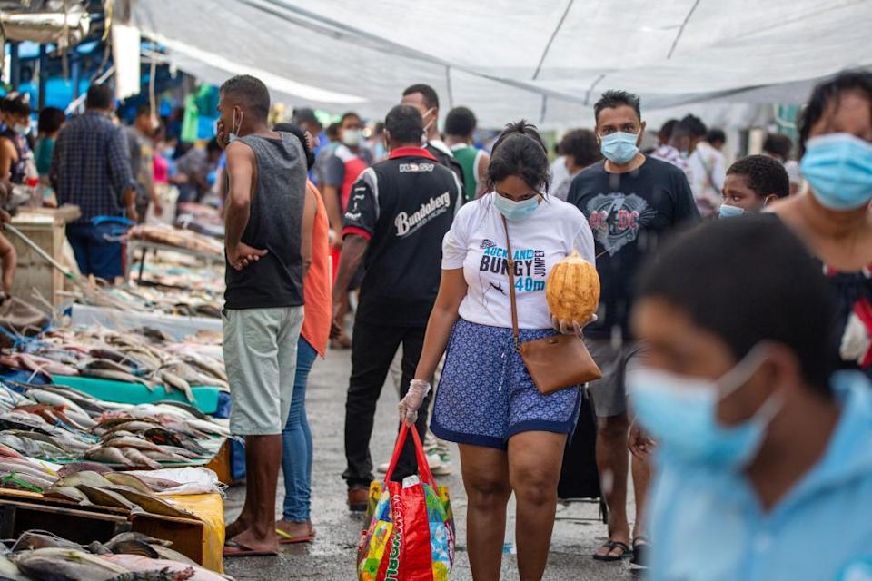 This picture taken on April 24, 2021 shows residents wearing face masks walking through the fish market in the Fijian capital Suva. Source: Getty