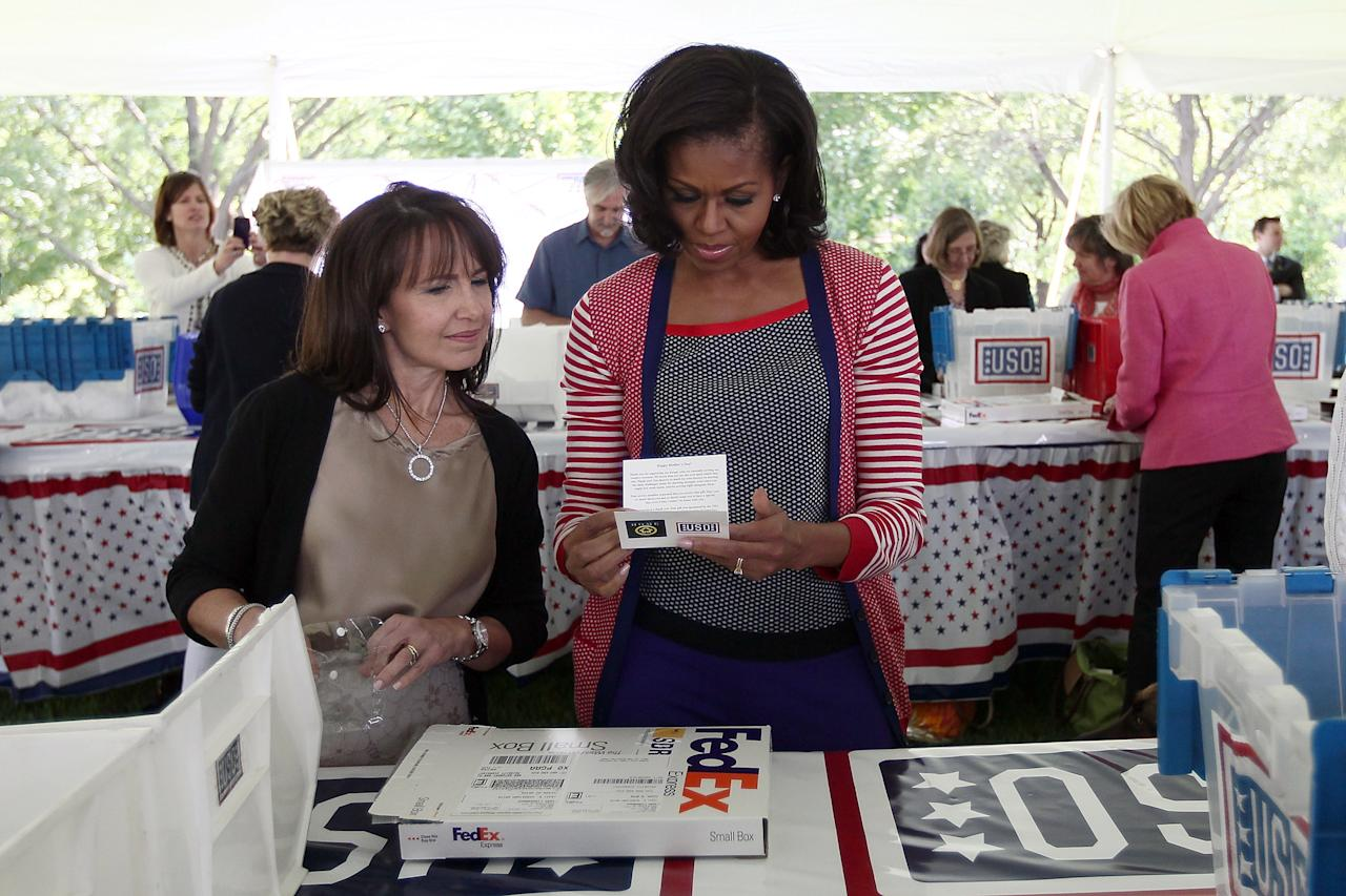 WASHINGTON, DC - MAY 10:  First lady Michelle Obama (R) participates in a Joining Forces service event at the Vice President's residence at the Naval Observatory May 10, 2012 in Washington, DC. Obama and Dr. Jill Biden joined with Congressional spouses to assemble Mother's Day packages that deployed troops have requested to be sent to their mothers and wives at home.  (Photo by Win McNamee/Getty Images)