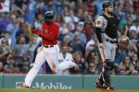 Boston Red Sox's Rafael Devers, left, scores behind Baltimore Orioles' Austin Wynns on an RBI-single by Xander Bogaerts during the seventh inning of a baseball game in Boston, Sunday, Sept. 29, 2019. (AP Photo/Michael Dwyer)