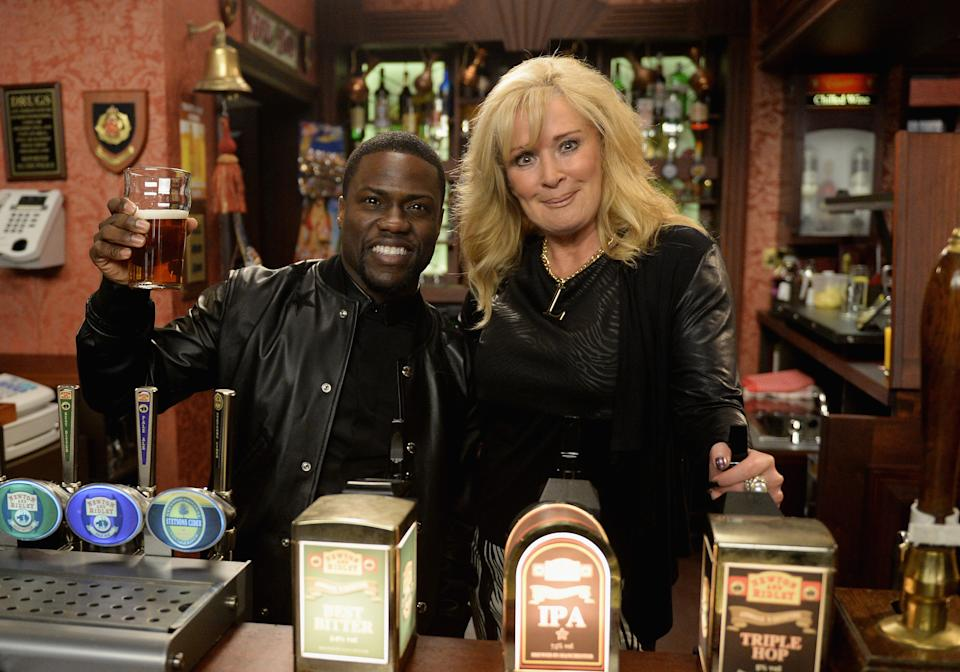 """MANCHESTER, ENGLAND - FEBRUARY 26:  Kevin Hart, star of """"Ride Along"""" makes a visit to the set of Coronation Street where he met Beverley Callard on February 26, 2014 in Manchester, England.  (Photo by Dave J Hogan/Getty Images)"""