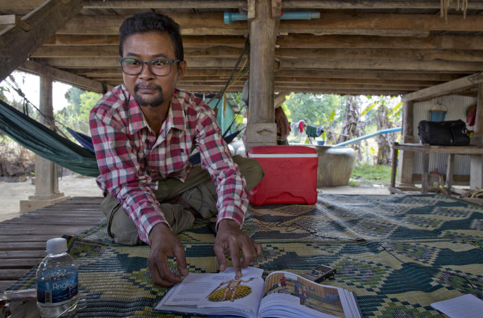 Vannak Anan Prum, who was double trafficked, points to his illustration of an abusive former boss, a palm oil estate owner, in his graphic novel depicting his life as a slave on a fishing boat before being sold onto a Malaysian palm oil plantation, at his home in Pursat, Cambodia, Saturday, March 30, 2019. (AP Photo/Gemunu Amarasinghe)