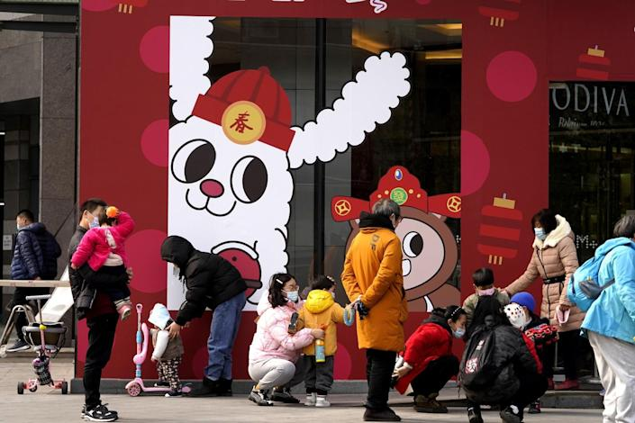 Wuhan residents and their children near Chinese Lunar New Year decorations.
