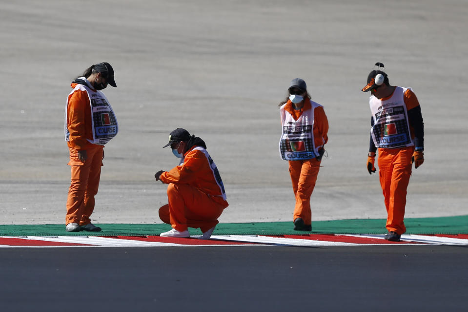 Stewatds check a manhole on the track during the third free practice session for the Formula One Portuguese Grand Prix at the Algarve International Circuit in Portimao, Portugal, Saturday, Oct. 24, 2020. The Formula One Portuguese Grand Prix will take place on Sunday. (Rafael Marchante, Pool via AP)