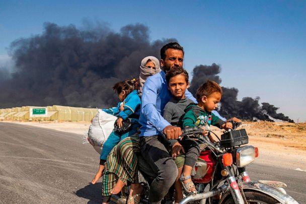 PHOTO: Displaced people, fleeing from the countryside of the Syrian Kurdish town of Ras al-Ain along the border with Turkey, ride a motorcycle together along a road on the outskirts of the nearby town of Tal Tamr on Oct. 16, 2019. (Delil Souleiman/AFP via Getty Images)
