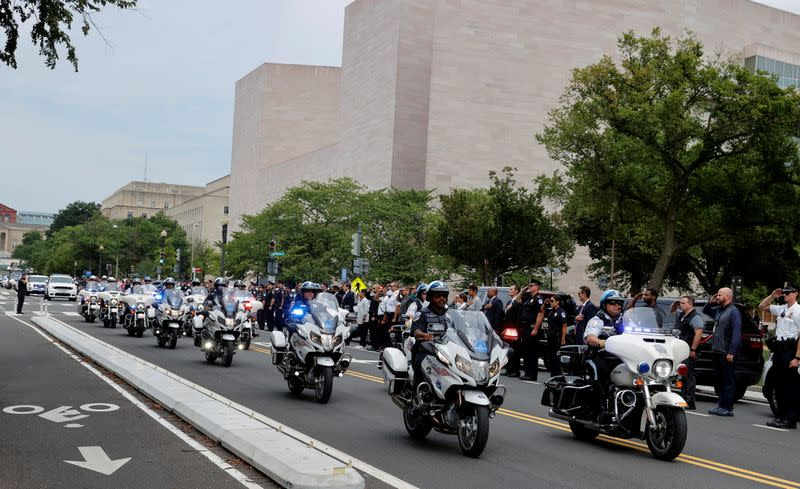Law enforcement officers salute as a ceremonial procession in honor of a police officer wounded outside the Pentagon earlier in the day passes the National Gallery in Washington