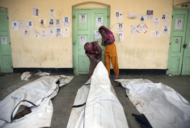 People cover their noses as they search through a line of dead bodies in hopes of identifying their relatives at a school turned make-shift morgue for victims of the garment factory building collapse, Thursday, May 2, 2013, in Savar, near Dhaka, Bangladesh. Rescuers found more bodies in the concrete debris of the collapsed garment factory building Thursday and authorities said it may take another five days to clear the rubble. In addition to the 430 confirmed dead, police report another 149 people are still missing in what has become the worst disaster for Bangladesh's $20 billion-a-year garment industry that supplies global retailers. (AP Photo/Wong Maye-E)