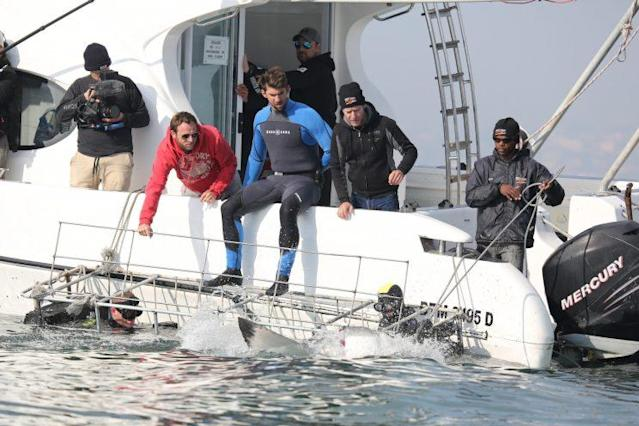Michael Phelps and the crew watch a shark approach the cage, which Phelps is about to enter. (Photo: Discovery)