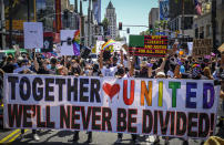 FILE - This photo from Sunday June 14, 2020, shows protesters holding up a banner calling for unity, during an All Black Lives Matter march, organized by black LGBTQ+ leaders in Los Angeles. The chaos unleashed in 2020, amid the coronavirus pandemic, has created space for different voices to speak, for different conversations to be had and for different questions to be asked. (AP Photo/Paula Munoz, File)