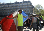 A man drapes himself in the French flag during a yellow vest demonstration in Paris, Saturday, April 20, 2019. French yellow vest protesters are marching anew to remind the government that rebuilding the fire-ravaged Notre Dame Cathedral isn't the only problem the nation needs to solve. (AP Photo/Michel Euler)