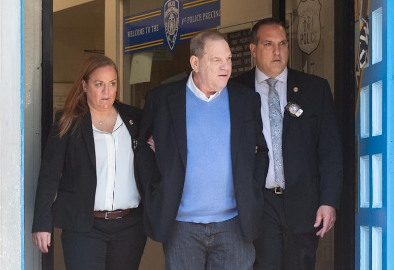 Harvey Weinstein, center, was led out of the New York City Police Department's First Precinct in handcuffs (AFP Photo/Bryan R. Smith)
