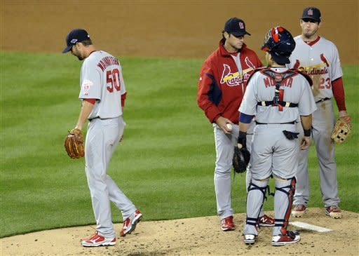 St. Louis Cardinals starting pitcher Adam Wainwright, left, walks off the field after being relieved in the third inning of Game 5 of the National League division baseball series against the Washington Nationals on Friday, Oct. 12, 2012, in Washington. At right are St. Louis Cardinals manager Mike Matheny, catcher Yadier Molina and third baseman David Freese. (AP Photo/Nick Wass)