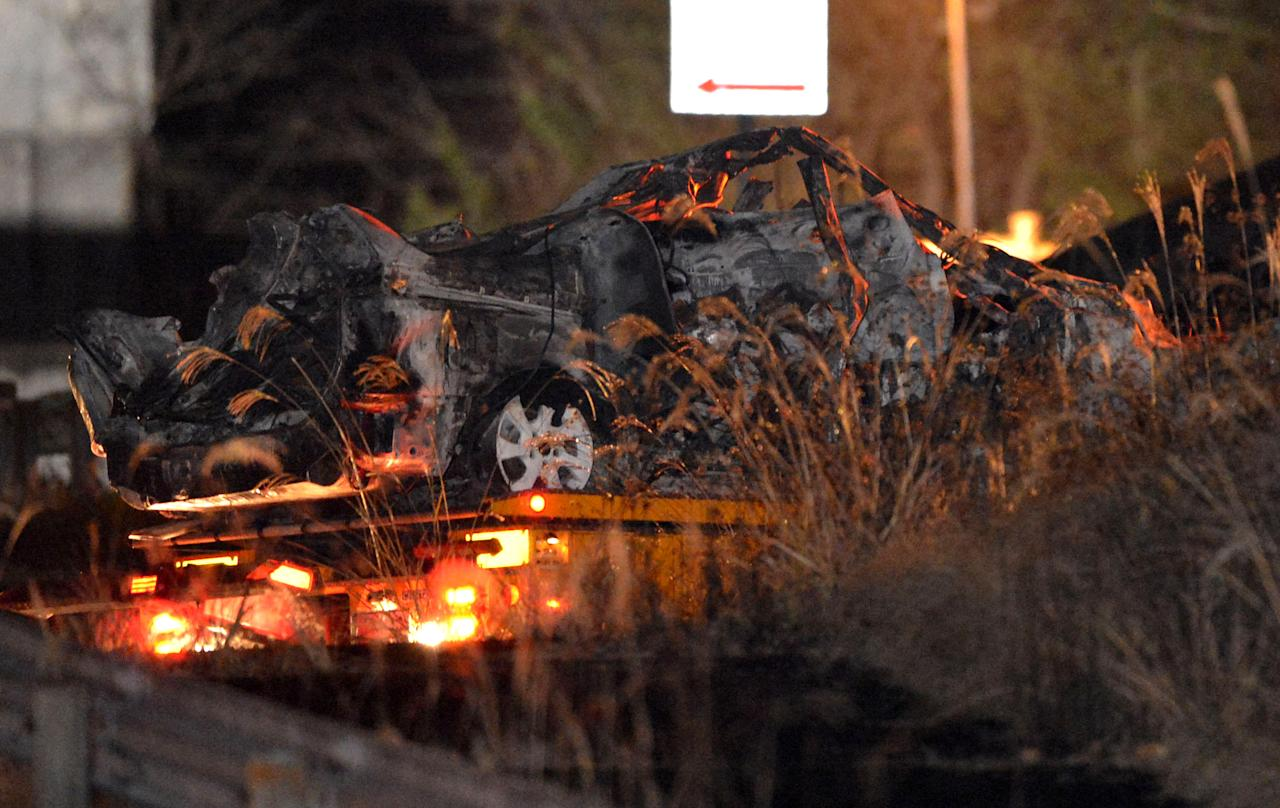 The burnt wreckage of a minivan, which was crushed and caught fire in Sunday's accident, is moved on a transporter out of the Sasago Tunnel on the Chuo Expressway in Koshu, Yamanashi Prefecture, central Japan, early Monday, Dec. 3, 2012. Concrete ceiling panels fell onto moving vehicles deep inside the tunnel, and authorities confirmed nine deaths before suspending rescue work Monday while the roof was being reinforced to prevent more collapses. (AP Photo/Kyodo News) JAPAN OUT, MANDATORY CREDIT, NO LICENSING IN CHINA, FRANCE, HONG KONG, JAPAN AND SOUTH KOREA