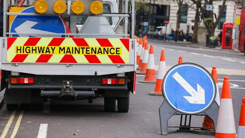 London street barricaded with Highway Maintenance vehicle and traffic cones