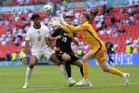 England's goalkeeper Jordan Pickford, right, goes for the ball ahead of England's Tyrone Mings, left, and Croatia's Bruno Petkovic during the Euro 2020 soccer championship group D match between England and Croatia, at Wembley stadium, London, Sunday, June 13, 2021. (Laurence Griffiths, Pool via AP)