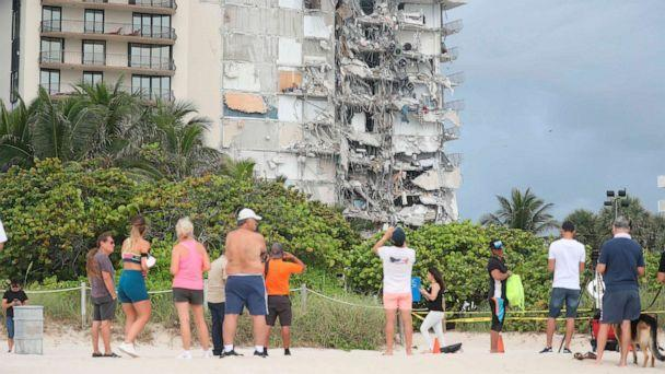 PHOTO: People look at the damage at the 12-story oceanfront Champlain Towers South Condo that collapsed early Thursday, June 24, 2021, in Surfside, Fla. (Susan Stocker/South Florida Sun Sentinel via AP)