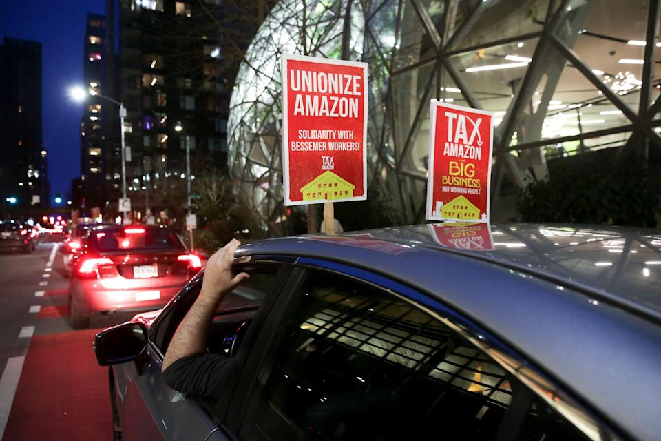 A sign supporting Amazon workers unionizing in Bessemer, Alabama, is pictured on a car during a Tax Amazon Car Caravan and Bike Brigade around the Amazon Spheres to defend a payroll-based tax on big businesses, including Amazon, that passed last July in Seattle, Washington, on Feb. 20. (Photo: JASON REDMOND/AFP/Getty Images)