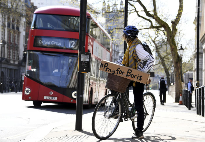 A woman with a #PrayForBoris sign on her bicycle in central London as the PM was in intensive care fighting the coronavirus. (AP)