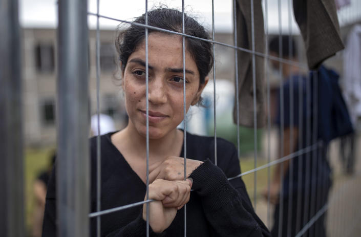 Saqd Ado, a migrants from Iraq, stands at the fence at the refugee camp in the village of Verebiejai, some 145km (99,1 miles) south from Vilnius, Lithuania, Sunday, July 11, 2021. Migrants at the school in the village of Verebiejai, about 140 kilometers (87 miles) from Vilnius, haven't been allowed to leave the premises and are under close police surveillance. Some have tested positive for COVID-19 and have been isolated in the building. (AP Photo/Mindaugas Kulbis)