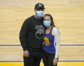 "Shelby Delaney, right, an intensive care unit nurse at Oakland's Alta Bates Summit Medical Center, and her husband, Robert Crowley, pose for a photo before the Golden State Warriors and Sacramento Kings NBA basketball game on Sunday, April 25, 2021, in San Francisco. Last spring, Stephen Curry placed a FaceTime call to Delaney and her colleagues at Oakland's Alta Bates Summit Medical Center after learning she was wearing his No. 30 jersey under her scrubs as inspiration to get through each trying day of the pandemic. Delaney wore the uniform again as she and Crowley sat on the floor for Sunday's game after a season ticket holder who couldn't attend gifted her the seats. Inside the jersey reads, ""I Can Do All Things."" (AP Photo/Tony Avelar)"