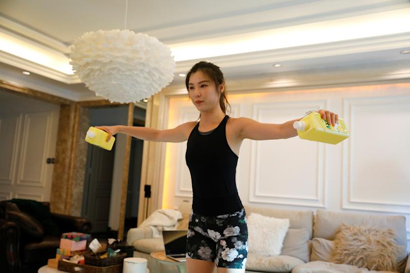 Zhang Weiya, a fitness trainer, uses bottles of dishwashing detergent as she livestreams a class at her house, as the country is hit by an outbreak of the new coronavirus, in Beijing, China February 15, 2020. Picture taken February 15, 2020. REUTERS/Carlos Garcia Rawlins