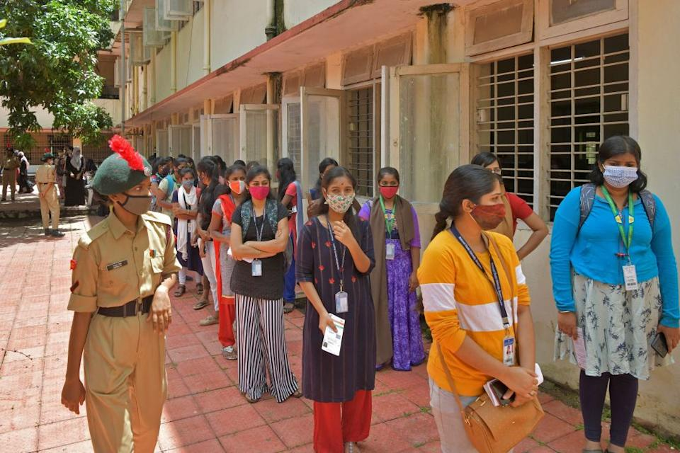 College students stand in queues as they wait for their turn to register themselves for a dose of the Covid-19 coronavirus vaccine in Bangalore.