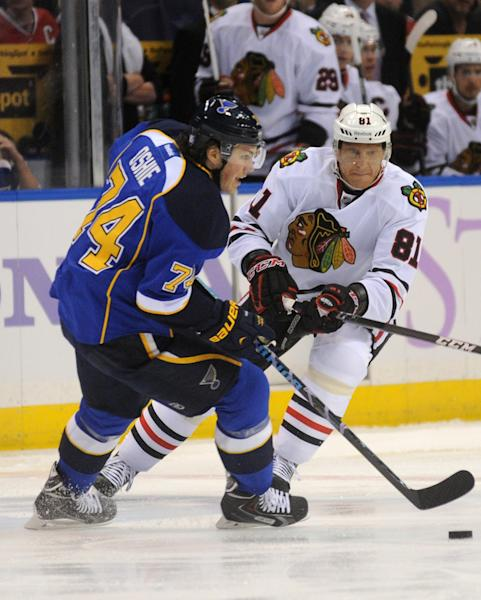 Chicago Blackhawks' Marian Hossa (81), of Slovakia, passes around St. Louis Blues' T.J. Oshie during the first period of an NHL hockey game Wednesday, Oct. 9, 2013, in St. Louis. (AP Photo/Bill Boyce)
