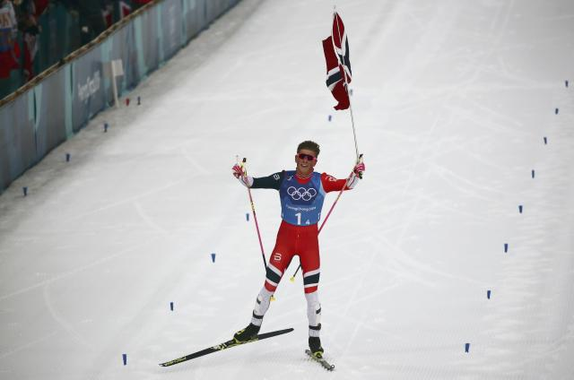 Cross-Country Skiing - Pyeongchang 2018 Winter Olympics - Men's 4x10 km Relay - Alpensia Cross-Country Skiing Centre - Pyeongchang, South Korea - February 18, 2018 - Gold medallist Johannes Hoesflot Klaebo of Norway holds his national flag. REUTERS/Carlos Barria