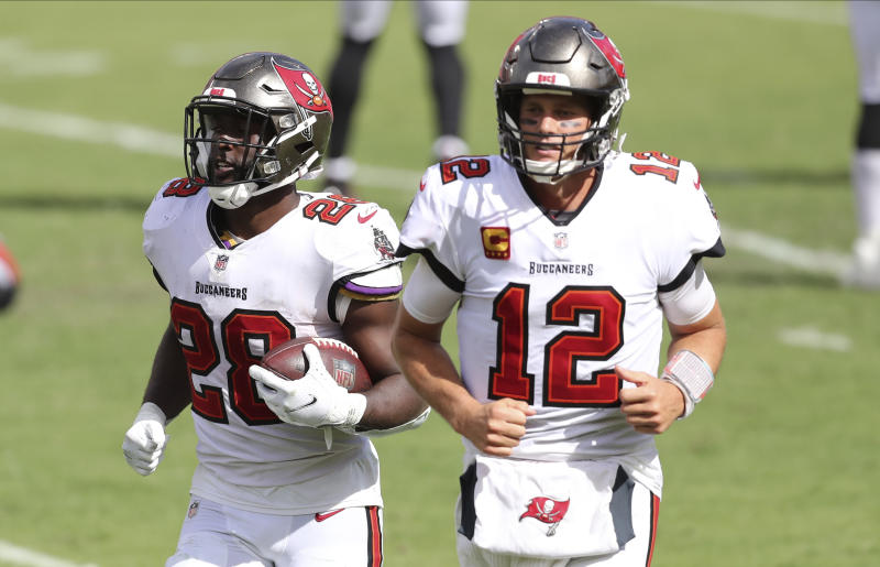 Tampa Bay Buccaneers running back Leonard Fournette (28) runs off the field with quarterback Tom Brady (12) after Fournette rans for a score against the Carolina Panthers during the second half of an NFL football game Sunday, Sept. 20, 2020, in Tampa, Fla. (AP Photo/Mark LoMoglio)