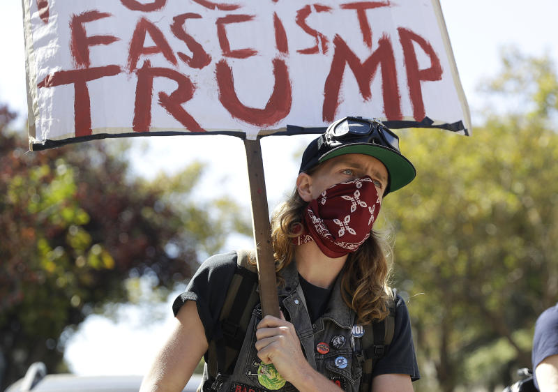 A protester holds up a sign outside of Alamo Square Park in San Francisco, Saturday, Aug. 26, 2017. SanFranciscoofficials took further steps Saturday to prevent violence ahead of a planned news conference by a right-wing group. Officials erected fencing and a large contingent of police monitored Alamo Square park, where the group Patriot Prayer was set to hold its event. (AP Photo/Marcio Jose Sanchez)