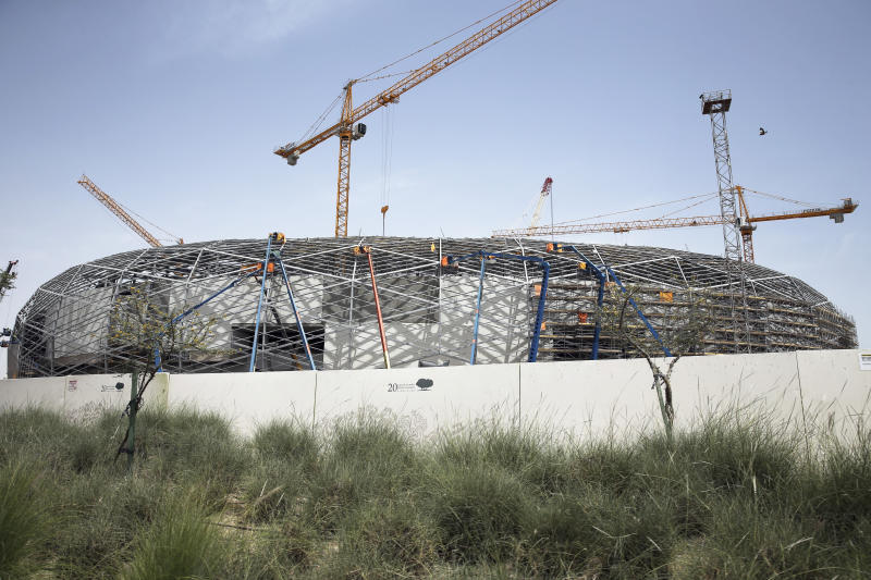 In this Friday, April 26, 2019 photo, cranes surround Qatar Foundation Stadium, an open cooled stadium with a 45,350-seat capacity. It is located in the middle of several university campuses at the Qatar Foundation's Education City in Doha, Qatar. Construction teams are working around the clock to complete eight stadiums ahead of the 2022 World Cup. (AP Photo/Kamran Jebreili)