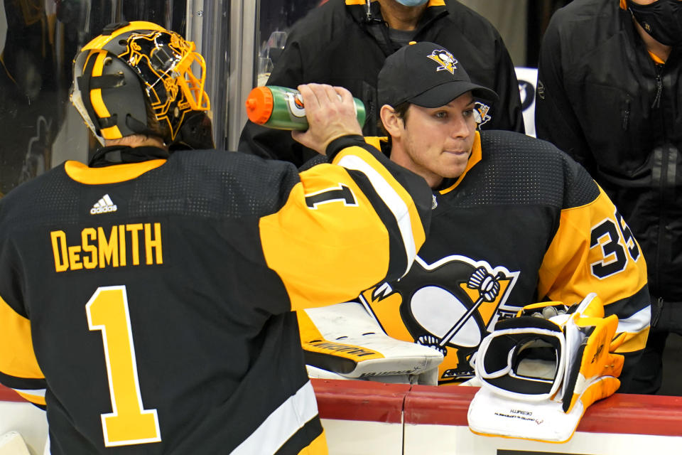 Pittsburgh Penguins goaltender Casey DeSmith (1) drinks during a timeout with goaltender Tristan Jarry (35) sitting on the bench during the third period of an NHL hockey game against the Washington Capitals in Pittsburgh, Sunday, Jan. 17, 2021. (AP Photo/Gene J. Puskar)