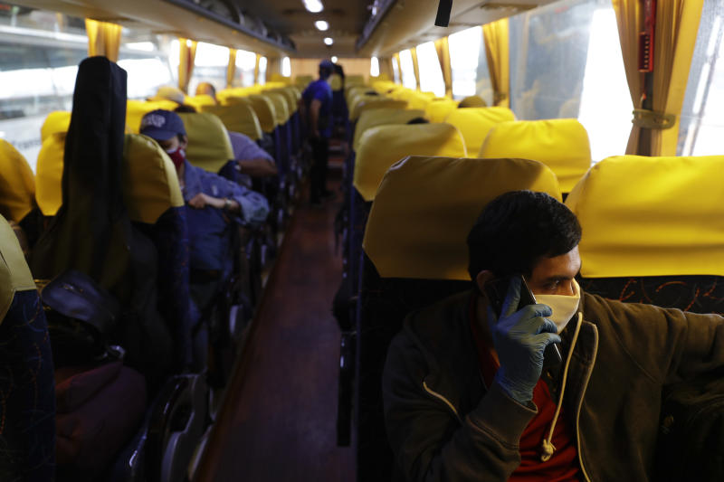 Christopher Bagay, right, a kitchen crew of the Aida Sol cruise ship in Europe, talks on his phone as he heads home together with other overseas Filipino workers on a government provided bus ride in Manila, Philippines Thursday, May 28, 2020. Bagay said it took him about two months to go through repetitive quarantines in Spain, Germany and Manila before he was finally allowed to go home. Tens of thousands of workers have returned by plane and ships as the pandemic, lockdowns and economic downturns decimated jobs worldwide in a major blow to the Philippines, a leading source of global labor. (AP Photo/Aaron Favila)