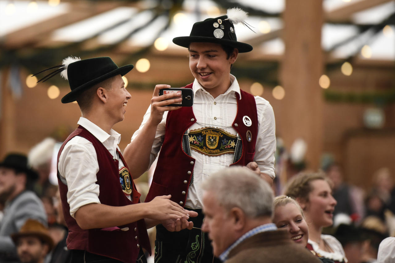 <p>Boys in traditional outfits take photos in one of the tents (Getty Images) </p>