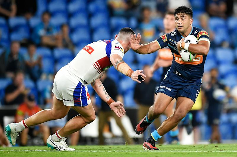 Tyrone Peachey of the Titans is tackled by Bradman Best of the Knights during the round 20 NRL match between the Gold Coast Titans and the Newcastle Knights.