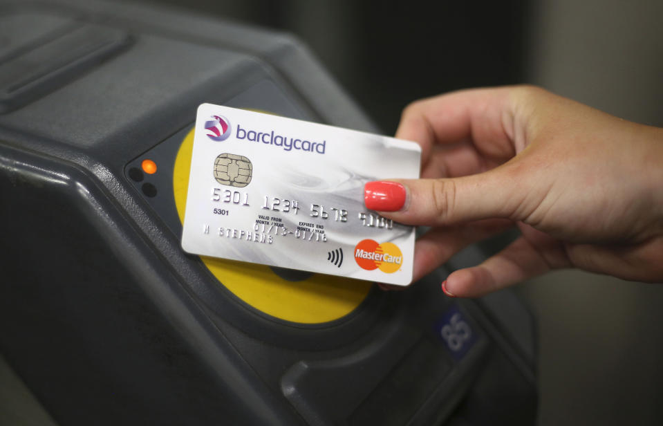 **Card used for this image is a fake** A customer at a the ticket barrier at Canary Wharf underground station in London using the new contactless payment being introduced on the tube, tram, DLR London Overground and National Rail services that accept Oyster.