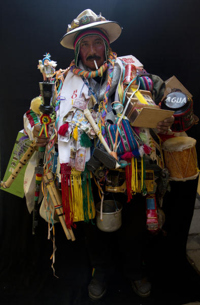 "In this Feb. 6, 2018 photo, Juan Ricaldi, dressed as ""Ekeko,"" the god of prosperity, is covered in objects including instruments as he holds a cigarette in his mouth during a portrait session on the sidelines of the annual Alasita Fair in La Paz, Bolivia. ""For me, the Ekeko hasn't made me rich but allows me to live,"" said the 59-year-old artisan. ""I can say that the Ekeko has made my dreams come true, has never left me and will be with me forever,"" he said. Ricaldi won this year's Ekeko competition. (AP Photo/Juan Karita)"