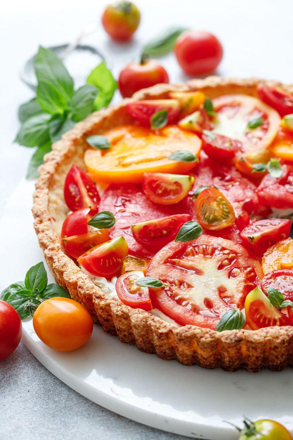 """<p>A savory parmesan shortbread crust is topped with a creamy basil goat cheese, then studded with an array of juicy vine-ripe tomatoes.</p><p><a href=""""https://www.loveandoliveoil.com/2020/07/goat-cheese-heirloom-tomato-tart.html"""" rel=""""nofollow noopener"""" target=""""_blank"""" data-ylk=""""slk:Get the recipe."""" class=""""link rapid-noclick-resp"""">Get the recipe. </a></p>"""