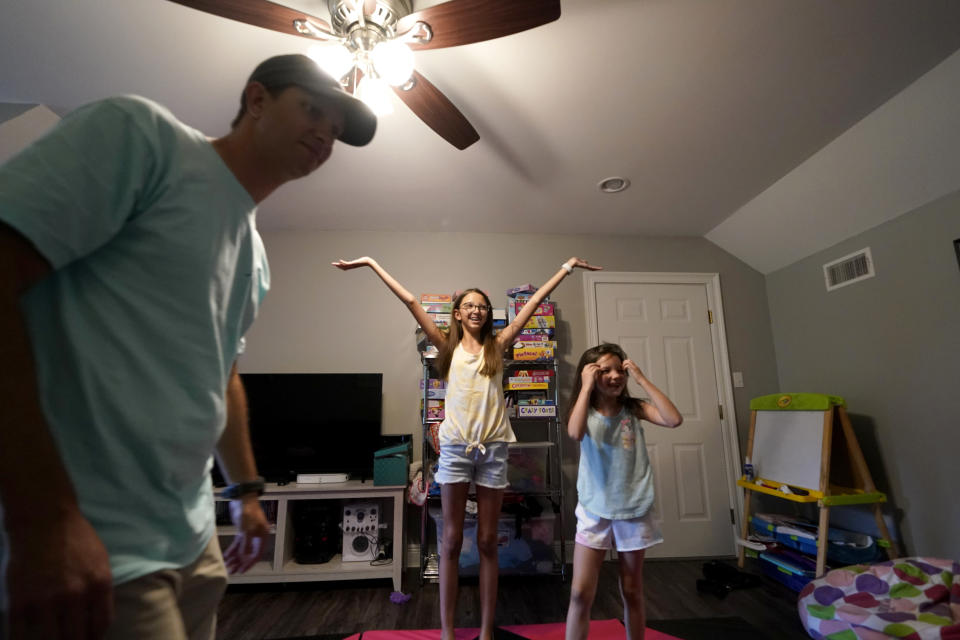 Cecilia Shaffette, center, reacts after doing a dance routine with her sister Lydia, in front of her father Rhett Shaffette at their home in Carriere, Miss., Wednesday, June 16, 2021. Twelve-year-old Cecilia is thriving, eight months after getting a portion of her father's liver. She received the transplant after nearly losing her life to internal bleeding. (AP Photo/Gerald Herbert)