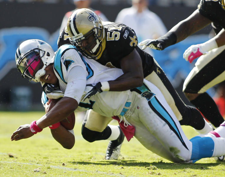 In this Oct. 9, 2011, photo, Carolina Panthers' Cam Newton, left, is tackled by New Orleans Saints' Jonathan Vilma (51) during an NFL football game in Charlotte, N.C. The suspensions of Vilma and three other players in the NFL's bounty investigation were lifted Friday, Sept. 7, 2012, by a three-member appeals panel and the league reinstated those players a few minutes later. The ruling does not permanently void their suspensions. (AP Photo/Bob Leverone)