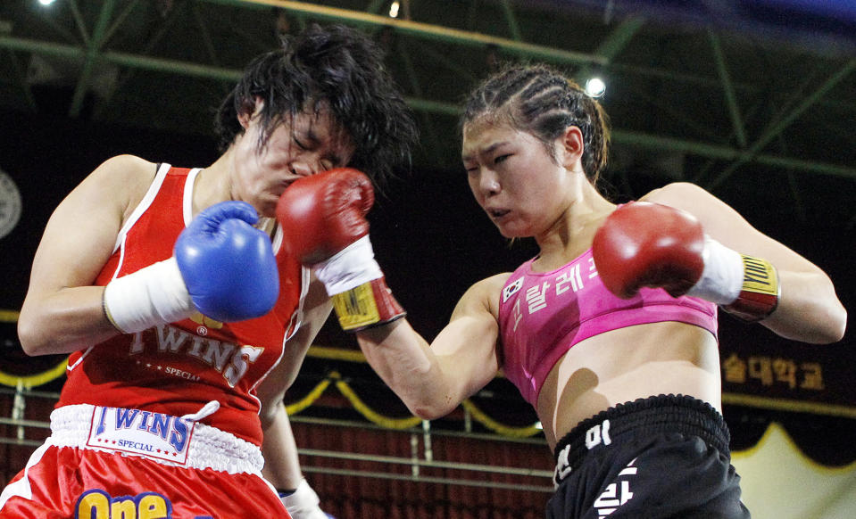 FILE - In this Dec. 17, 2011, file photo, South Korean champion Choi Hyunmi, right, a former North Korean defector, lands a right to challenger Sainamdoy Pitaklongen of Thailand during their WBA women's featherweight title boxing bout in Seoul, South Korea. South Korea's only boxing world champion is Choi, a North Korean defector who fled her authoritarian homeland as a 13-year-old girl with her family in 2003. (AP Photo/Lee Jin-man, File)