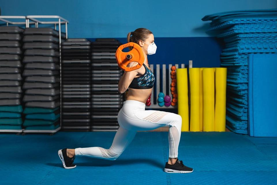woman doing lungs at the gym wearing n95 face mask