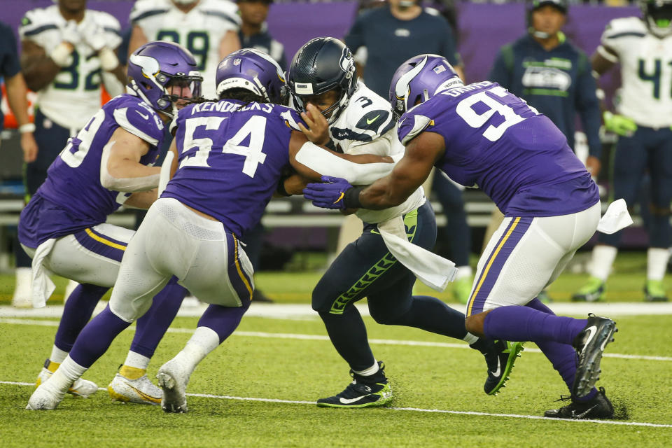 Seattle Seahawks quarterback Russell Wilson (3) is tackled by Minnesota Vikings middle linebacker Eric Kendricks (54) and defensive end Everson Griffen (97) in the second half of an NFL football game in Minneapolis, Sunday, Sept. 26, 2021. (AP Photo/Bruce Kluckhohn)