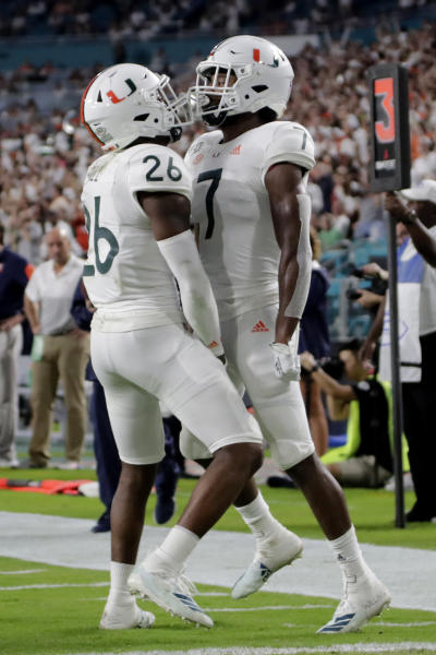 Miami cornerback Al Blades Jr. (7) celebrates with defensive back Gurvan Hall Jr. (26) after breaking up a pass intended for Virginia wide receiver Terrell Chatman during the first half of an NCAA college football game, Friday, Oct. 11, 2019, in Miami Gardens, Fla. (AP Photo/Lynne Sladky)